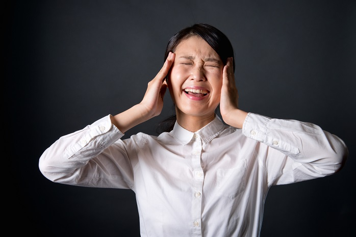 頭痛で頭を抱える女性