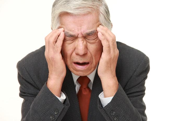 頭痛のためこめかみを抑えるシニアの男性