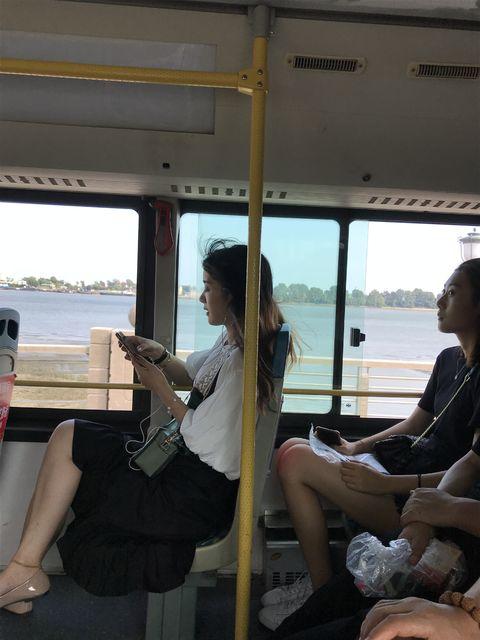北朝鮮の車窓をバックにスマホをいじる若い女性たち